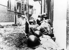 Imperial Japanese soldiers are photographed in street battle with soldiers of the Chinese National Army during the Battle of Shanghai of the Second Sino-Japanese War. In the background can be seen support from a Japanese Type 89 I-Go medium tank. Shanghai, Republic of China. August 1937.