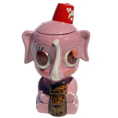 "Designed by Mitch O'Connell many years ago Munktiki Imports is now ready to  bring the Pink Elephant to the general public for your viewing and buying  pleasure. Behold the massiveness of the Pink Elephant...... with a  Fez....... and a Moai.   To help remind you ""Never Forget to Get Drunk"" is written on the back the  mug. From the top to the bottom Pink Elephant is 8 1/2 inches tall and  holds 3 full cups, that's just a cup shy of a quart! Remove lid, fill up  with booze, replace lid…"