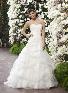 Sincerity wedding dress style 3721 A tulle pick-up ball gown that is complemented by an asymmetrical drop  waist. This style has a sweetheart neckline done in beaded lace and 3D  flowers. It also has a lace up back and a pick-up chapel length train.