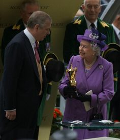 Prince Andrew, the Duke of York presents Britain's Queen Elizabeth II with a trophy after her horse Estimate won the Gold Cup, during day three of the Royal Ascot 2013