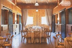 Soft rustic fall wedding with crossback chairs in a horse barn with horse stables and stalls.