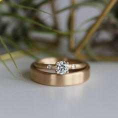 Our 5mm Crown Solitaire with side stones and a 5x2mm Edgeless Flat Band, both pictured in yellow gold.