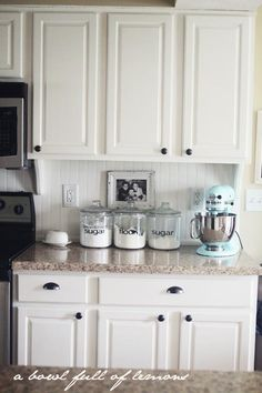Example of a lighter 'cookies and cream' colored countertop with the white cabinets and dark colored hardware...