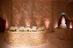 feathered back drop | sweetheart table covered in white roses | custom, mirrored stage | draped ballroom in sheer, white fabric | mirrored table tops, candles and soft lighting