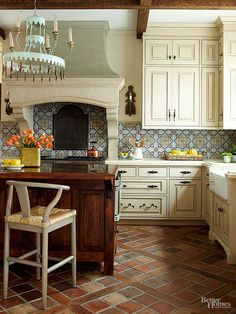 Tuscan kitchens are renowned for putting ordinary materials on display. A humble terra-cotta tile floor is elevated into a stunning architectural feature when laid on the bias and bisected by salvaged wood.