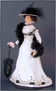 Edwardian lady. Her beautiful silk dress has 8 gores and has a high waistline. On the black and white striped hemline is a lace appliqué. The underbodice is of silk, covered with lace.