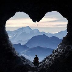 ⭐Love this view⭐ A lone man sits in the middle of a heart-shaped opening in a cave. In the distance, we can see snow-capped mountains and clear blue skies.