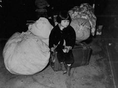 A young Japanese-American girl awaiting bus for internment camp, California, Apr 1942.