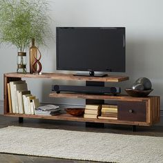 I kind of like this staggered wood console. Open shelf for a sound bar. Thick metal plate down the center to hide cords. Uneven wood surface. Way too wide for my room but shouldn't be too hard to whip up a shorter version.