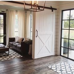 Wood floors + black steel door frame windows + sliding wood door / fixer upper hgtv