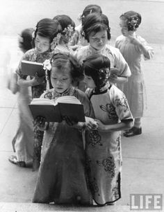 Eight little Chinese-American girls wearing embroidered tunics & beaded ornaments in their hair, snatch a peak at their lesson books before filing into their classrooms at the only Catholic Chinese school in the US. San Francisco, 1936.  By Alfred Eisenstaedt
