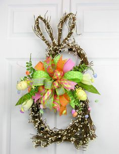 A vine and white gypsum grapevine bunny shaped wreath with a six patterned multi Terri Bow. The wreath has accents of whispy egg picks, tulips, ferns and Easter egg picks. (Easter egg and tulips may v