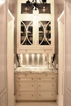 classic cream cabinets -love the muntin design, thin drawer in the bottom of the upper cabinet, and the FABULOUS corbel brackets - interesting walls; silver leaf maybe? oh and of course, the marble countertop!