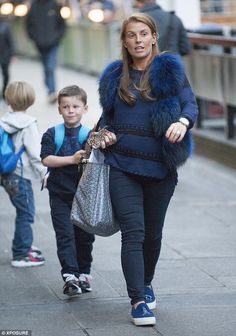So sweet: Pregnant Coleen Rooney went make-up free and covered up her bump as she headed t...