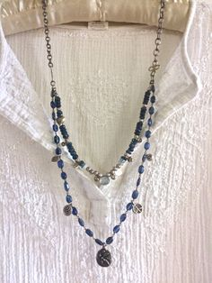 this beautiful gemstone double strand necklace is a perfect london blue navy thats great with blue jeans! its bottom strand is a beaded chain of london blue quartz with peace/love/om charms on it... in the center is a circular pewter flying fairy pendant with the word fly on the back!  the upper strand is navy blue apatite beaded chain with silver thai beads and city charms that meets in the center with a light blue topaz teardrop briolette! these strands meet at the sides with artisan…