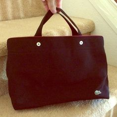 Black Lacoste bag! Good condition. Black with maroon interior and piping at top. White button detail on front and back. Open to offers! Size is approximately 8x12x5 canvas material. Lacoste Bags Totes