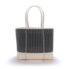 Large Black + White Palorosa Tote Bag: Founded in 2014 by architect and landscape gardener, Cecilia Pirani, The Palorosa Project designs and produces hand woven baskets and objects inspired by Guatemala City and the country's landscape. Working closely with local artisans, Palorosa merges design with artisan in an effort to promote craft-preservation and local manufacture.  Hand woven in Guatemala incorporating recycled plastic, each tote has a sand coloured base with a bi-colour combination…