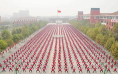 A Chinese national flag flies as students practice Taichi on a playground of a high school, during a Guinness World Record attempt of the largest martial arts display, on a hazy day in Jiaozuo, Henan province, China, October 18, 2015. The city successfully set the record by organizing over 50,000 residents to practise shadow boxing simultaneously at 15 different locations on Sunday morning