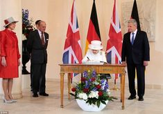 Signing on the line: The Queen signs the guest book at the Schloss Bellevue watched by President Gauck of Germany and Prince Philip