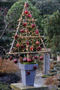 Bamboe is de basis van deze alternatieve kerstboom, waarin lampjes, sterren en appels zijn gehangen. In plaats van appels kun je ook kerstballen, dennenappels of linten gebruiken als versiering. #zelfmaken #natuurlijkematerialen #kerst
