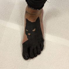 Black tattoo of a Batman inked on the left foot
