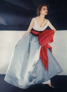 Jacques Fath's most dramatic evening dress, mmade of three separate pieces. A foreshortened bodice of white chiffon, cowl draped and a fascia of black satin slashed with cherry red looped over a blue satin skirt. Photo by Horst P. Horst.