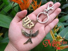 "This keychain features two charms, one of the Mockingjay in flight, and ""D13"", the logo of District 13. The bronze plated Mockingjay charm measures 4 cm by 3 cm"