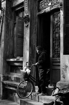Older man with his bicycle leaving his cool French colonial style house, Hanoi, Vietnam.