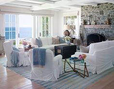 Ceiling treatment and Big, comfortable sofas and chairs slipcovered in white cotton denim and a durry rug. Walls are Benjamin Moore's White Heron. The blue print throw is from Hermès.