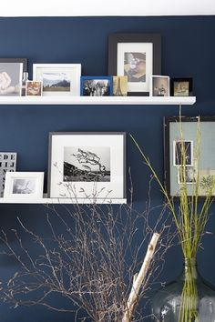 The white picture ledges from Ikea make up a gallery wall, of which the most prominent print is by Doreen Kilfeather. The bedroom keeps in with the dark blue tone of the apartment and is painted in Farrow & Ball Hague. Dark Blue Lounge, Dark Blue Walls, Navy Walls, Ikea Picture Ledge, Picture Shelves, Grey Shaker Kitchen, Gallery Wall Bedroom, Bedroom Colors, Bedroom Ideas