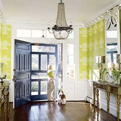 Big and open country house style foyer with terrific chartreuse damask print wallpaper. Oversized front door and storm door are both painted a brilliant shade of marine blue (and look how huge the transom and sidelights are).