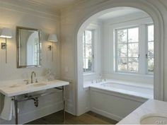 An all white modern bathroom with double sinks and a bath tub with beautiful views. Westport, CT Coldwell Banker Residential Brokerage $8,250,000