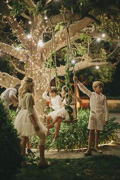 Children on a Fairy light garden swing | Destination wedding in Castellón Spain, near the Mediterranean Sea | Pastel colour scheme | DIY decor | Images by Volvoreta Bodas | http://www.rockmywedding.co.uk/adri-igor/: