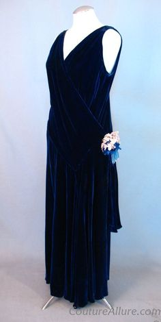 1920s flapper era dress fashioned of luxurious royal blue silk velvet and has the angled seams that are a hallmark of this era. The front bodice has a surplice neckline that can drape as high or low as you want. Smocking stitches accent each shoulder and the right hip. A silk posy decorates the right hip