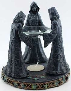 """The Maiden, Mother, and Crone gather together around the flame of a tealight candle, supporting a glass vessel in their upturned palms. Made out of cold-cast resin and decorated with hand painted vines and ivy, this 6"""" tall oil diffuser uses the heat of a tealight candle beneath a glass bowl to release the scent of your favorite oil throughout your sacred spaces. The base of this piece is sturdy; 5 3/4"""" in width and quite thick"""