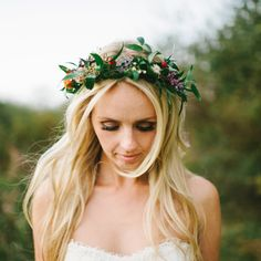 Brides.com: The Prettiest Wedding Hairstyles with Flower Crowns. An Autumnal Floral and Greenery Crown  For a fall wedding, channel seasonal hues and blooms. This bride mixes crisp greenery with flowers in various shades of red, orange, and purple.