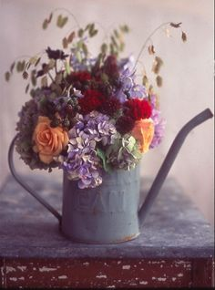 Place flowers in a variety of containers, such as watering cans, to get an old-fashioned and personalized feel.