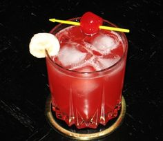 Tropical Orgasm ~ 1.5 oz. Vodka, 1 oz. Spiced Rum, 4 oz. Pink Lemonade, 1 oz. Strawberry Daiquiri Mix, Banana slice and/or Cherry for garnish