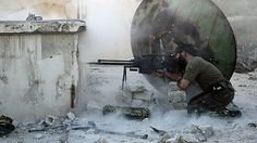 A rebel fighter with the Free Syrian Army shoots back at a sniper during clashes with pro-government forces in Aleppo's Karm al-Jabal distri...