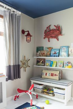 A corner of a white and blue nautical-themed nursery boasts open bookshelves and a comfy storage bench. Both of these kid-friendly storage options make playtime (and cleanup) a breeze.