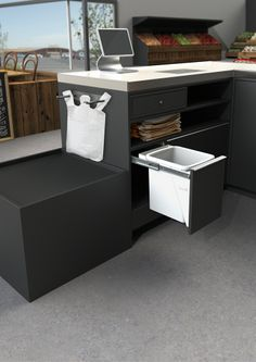 A 15L Hideaway Bin featured at a super market check out.