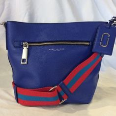 Marc Jacobs 'Gotham' Leather Bucket Bag Cobalt Blue. A racing-striped webbed crossbody strap adds a fresh, sporty look to a just-right bucket bag fashioned from pebbled leather. The deep, lined interior accommodates everyday essentials, while an exterior zip pocket keeps oft-used items close at hand. Magnetic snap-tab closure. Optional, adjustable crossbody strap. Exterior zip pocket. Interior zip, and smartphone pockets. Protective metal feet. Lined. Leather. NWOT Tags are included but not…