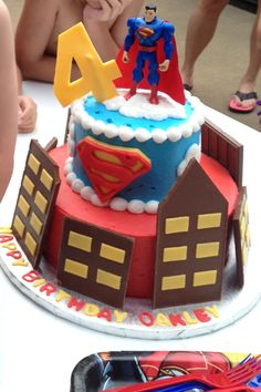 Superman cake. 6 and 10 inch cakes iced in buttercream icing. The four was cut from rolled fondant. The buildings were made from large Hershey's candy bars and the windows were cut from rolled fondant.