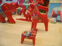 dala horses: one's looking at you, one's scratching his ear, and one's an... elephant?