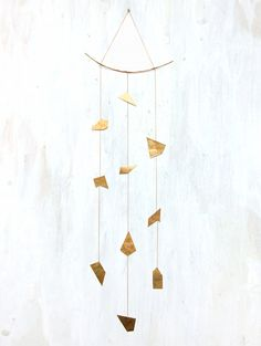 A 3 strand mobile for the home made with organic hand-cut and forged brass sheet and attached by a vintage brass chain, by fail HOME, handmade in Austin, TX