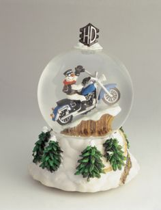 Close-up of a figurine riding a motorcycle in a snow globe