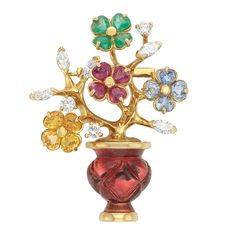 Gold, Carved Pink Tourmaline, Gem-Set and Diamond Clip-Brooch, by Marvin Schluger 18 kt., the floral bouquet embellished by four flowers set with 16 round rubies, yellow sapphires, sapphires and emeralds, altogether approximately 5.25 cts., accented by polished gold branches tipped by 3 round and 5 marquise-shaped diamonds approximately 1.50 cts., supported by a carved pink tourmaline vase, edged by polished gold