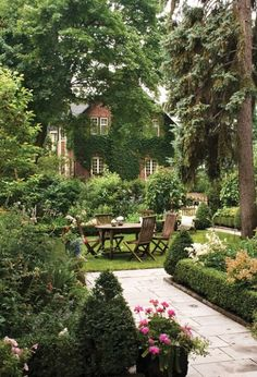 Beautiful outdoor dining with beautiful flowers, mature trees and boxwoods