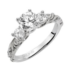 """Brides.com: Three-Stone Engagement Rings. Style 31-V101ERW, """"Fanciful"""" diamond three-stone engagement ring with round center, round side stones, and a floral carving detail highlighted with diamonds."""