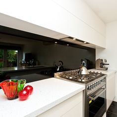 The boldness of a black, glass splashback; with beautiful white stone benchtop; and flush, push-to-open cabinetry.